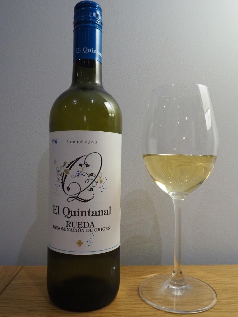 Бокал вина рядом с бутылкой испанского вина Вердехо на деревянном столе